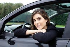Красивая женщина при большие глаза сидя в автомобиле усмехаясь смотрящ камеру с белыми зубами Стоковая Фотография