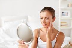 Красивая женщина при зеркало сидя на кровати дома Стоковое Фото