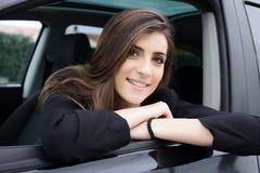 Красивая женщина при длинные шелковистые волосы сидя в усмехаться автомобиля Стоковые Изображения RF