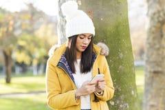 Красивая женщина при крышка смотря сообщение на телефоне, внешнем стоковые изображения rf