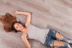 Красивая женщина при наушники лежа на поле Стоковое Изображение