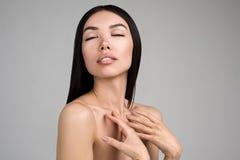 Красивая женщина при совершенный портрет кожи изолированный на серой предпосылке Стоковая Фотография