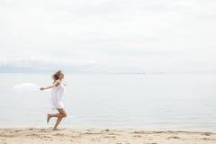 Красивая женщина при шарф чувствуя свободно на пляже Стоковое Фото