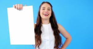 Красивая женщина проводя пустой плакат на голубой предпосылке акции видеоматериалы
