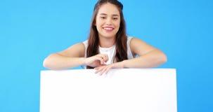 Красивая женщина проводя пустой плакат на голубой предпосылке видеоматериал