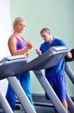 Красивая женщина работая в спортзале с личным тренером фитнеса Стоковая Фотография