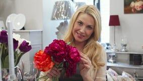 Красивая женщина рассматривает букет с цветками стоковое фото rf