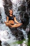 Красивая женщина сидя в естественном водопаде стоковая фотография