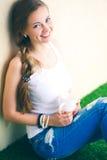 Красивая женщина сидя на поле и держа чашку красивейшая женщина Стоковое Изображение RF