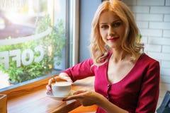 Красивая женщина сидя окном в кофе кафа выпивая стоковое фото