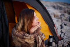 Красивая женщина сидя с рукой под подбородком, на каменном пляже, смотря заход солнца Стоковое Изображение RF