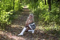 Красивая женщина сидела вниз в древесине осени, в среднем o Стоковая Фотография