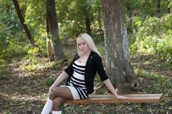Красивая женщина сидит на стенде в парке осени Стоковое Изображение RF