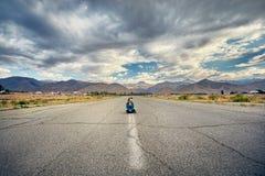 Красивая женщина сидя на дороге стоковое изображение rf