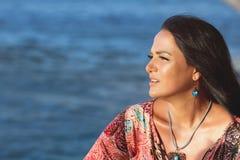 Красивая женщина сидя на пляже и наблюдая океан Стоковые Фото