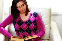Красивая женщина сидя на софе и читая книгу Стоковые Фото