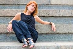 Красивая женщина сидя на шагах Стоковая Фотография