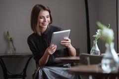 Красивая женщина сидя около окна используя планшет Стоковые Изображения