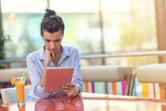 Красивая женщина смешанной гонки с афро стилем причесок держа цифровой планшет на кофейне стоковое фото rf