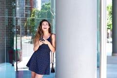 Красивая женщина смеясь над и стоя снаружи с мобильным телефоном Стоковые Изображения RF