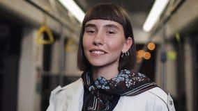 Красивая женщина смотря камеру в трамвае и усмехаясь, steadycam сняла : сток-видео