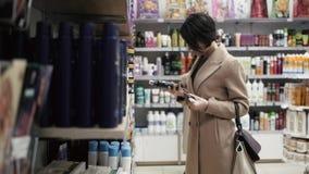 Красивая женщина смотря косметики в супермаркете сток-видео