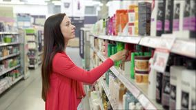 Красивая женщина смотря косметики в супермаркете Привлекательная девушка покупая косметические продукты Смотреть и выбор акции видеоматериалы
