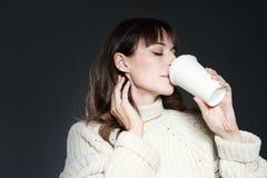 Красивая женщина со свитером длинных волос нося держит бумажную устранимую кофейную чашку Выпивая кофе с расслабленной стороной п стоковые фотографии rf