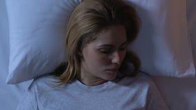 Красивая женщина спать в кровати, ослабляя вечером после длинного дня, взгляд сверху сток-видео
