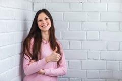 Красивая женщина стоит на предпосылке кирпича Стоковая Фотография RF