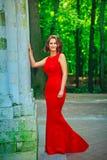 Красивая женщина стоя и усмехаясь в abeautiful естественном backg Стоковое Изображение RF