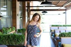Красивая женщина стоя на кафе около зеленых palnts Стоковая Фотография