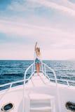 Красивая женщина стоя на носе яхты на солнечном летнем дне, волос ветерка превращаясь, красивого моря на предпосылке Стоковое Изображение RF