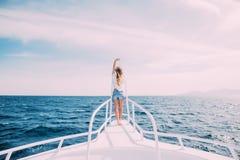 Красивая женщина стоя на носе яхты на солнечном летнем дне, волос ветерка превращаясь, красивого моря на предпосылке Стоковая Фотография RF