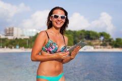 Красивая женщина стоя на пляже и принимая таблетку Стоковая Фотография RF