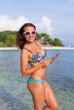 Красивая женщина стоя на пляже и принимая таблетку Стоковая Фотография