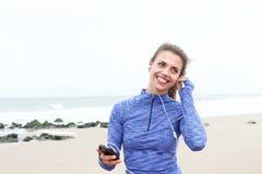 Красивая женщина стоя на пляже слушая к музыке Стоковое Фото