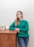 Красивая женщина стоя около комода ящиков Стоковое Фото