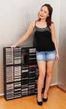 Красивая женщина стоя около счетчика с компактными дисками Стоковое Изображение