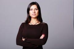 красивая женщина стоя при сложенные оружия стоковое фото