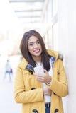 Красивая женщина счастья держа умный телефон в улице стоковое фото rf