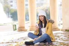 Красивая женщина счастья при крышка держа телефон в парке стоковое изображение rf