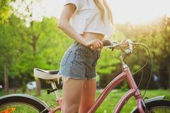 Красивая женщина с велосипедом в парке стоковые изображения rf