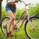 Красивая женщина с велосипедом в парке стоковое изображение