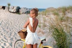 Красивая женщина с велосипедом на пляже Стоковая Фотография