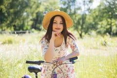 Красивая женщина с велосипедом на парке города красивейшая природа Стоковые Фотографии RF
