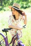 Красивая женщина с велосипедом на парке города красивейшая природа Стоковое фото RF
