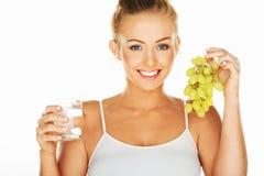 Красивая женщина с водой и виноградинами Стоковая Фотография