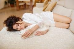 Красивая женщина с вьющиеся волосы в белом silk халате рано утром играя при белый пушистый кот сидя на софе Стоковые Изображения RF