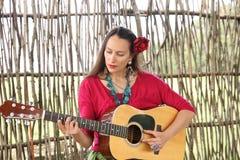 Красивая женщина с гитарой и красной розой в ее волосах стоковое фото
